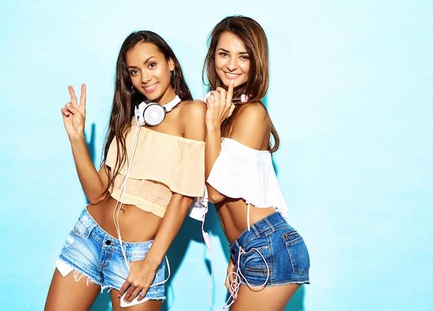 Dwie młode figlarne hipster kobiety w modne letnie ubrania i słuchawki. seksowne beztroskie kobiety słuchające muzyki. modele pozowanie w pobliżu niebieską ścianą