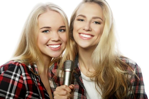 Dwie młode hipsterskie blond dziewczyny śpiewają na białym tle