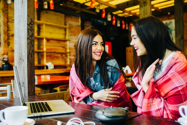 Dwie młode i piękne dziewczyny siedzą przy stole i szukają czegoś w internecie