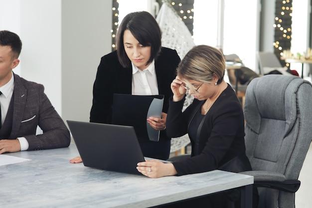 Dwie młode kobiety biznesu w biurze, analizując informacje zaglądając do laptopa.
