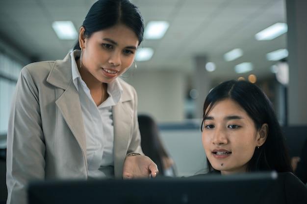 Dwie młode kobiety biznesu z azji pracujące razem w przestrzeni biurowej