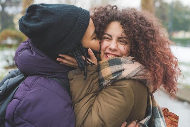 Dwie młode kobiety całują policzek