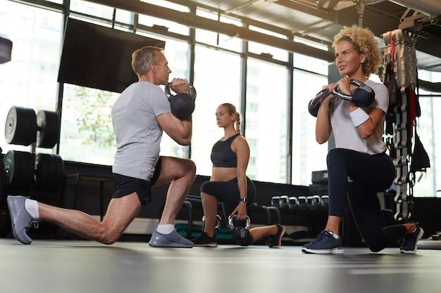 Dwie młode kobiety ćwiczenia z hantlami wraz z instruktorem na siłowni