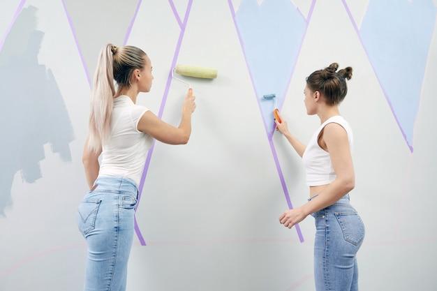 Dwie młode kobiety malują ścianę wałkiem do malowania i używają taśmy maskującej
