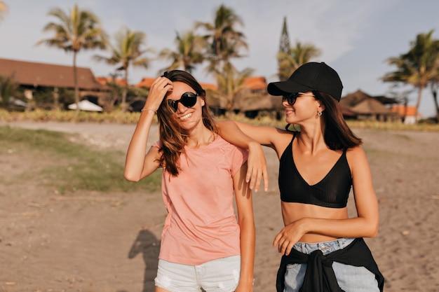 Dwie młode kobiety na plaży zabawy poczuć wolność na brzegu oceanu w pogodny dzień lata. przyjaciółki kobiet korzystających z wakacji na plaży