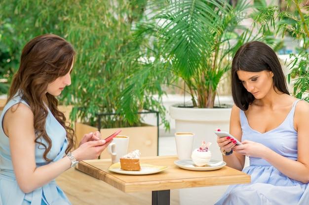 Dwie młode kobiety patrząc na swoje smartfony siedząc w kawiarni. uzależnienia od technologii