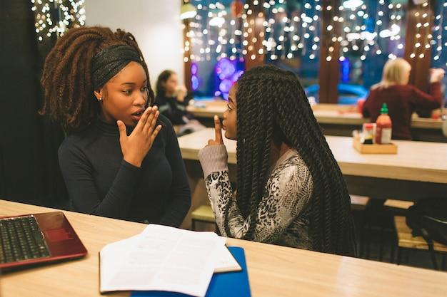 Dwie młode kobiety plotkują przy stole