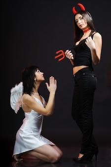 Dwie młode kobiety pozujące w kostiumach anioła i demona. dziewczyna klęczy i trzyma ręce przed twarzą