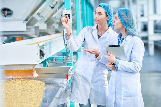 Dwie młode kobiety pracujące w nowoczesnej fabryce żywności