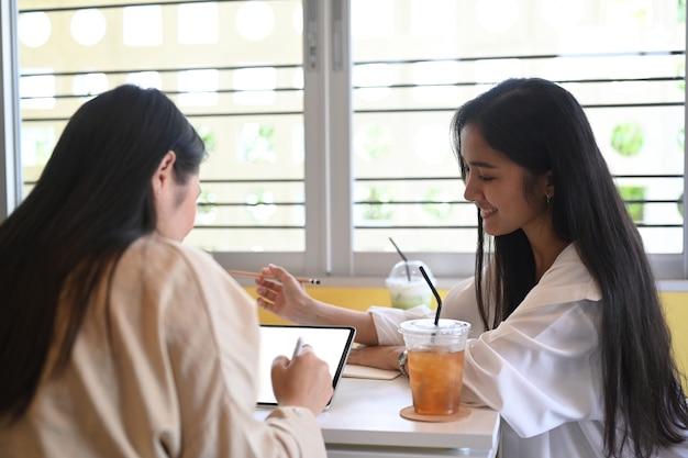 Dwie młode kobiety przedsiębiorca małej firmy planowania i dyskusji na temat swojego nowego projektu.