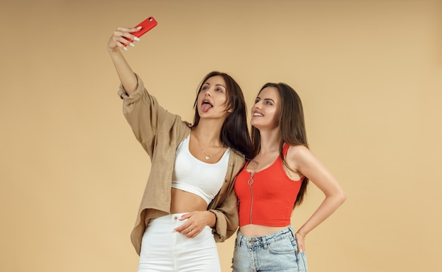 Dwie młode kobiety przy selfie na smartfonie na na białym tle beżowym tle