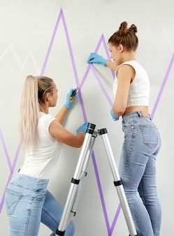 Dwie młode kobiety przygotowujące ścianę do malowania stojąc na drabinie nakładają taśmę maskującą na ścianę diy