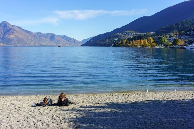Dwie młode kobiety relaks na plaży jeziora wakatipu, queenstown, wyspa południowa w nowej zelandii