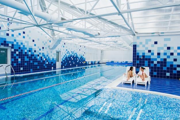 Dwie młode kobiety relaksujące się przy basenie w szlafrokach