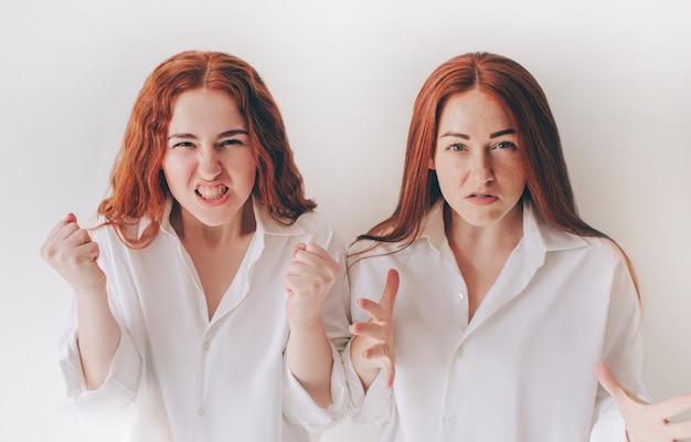 Dwie młode kobiety rozzłościły się i krzyczały do kamery. czują wściekłość, agresję, gniew. dwie rudowłose siostry stoją na białym tle na białym tle w obszernych dużych koszulach