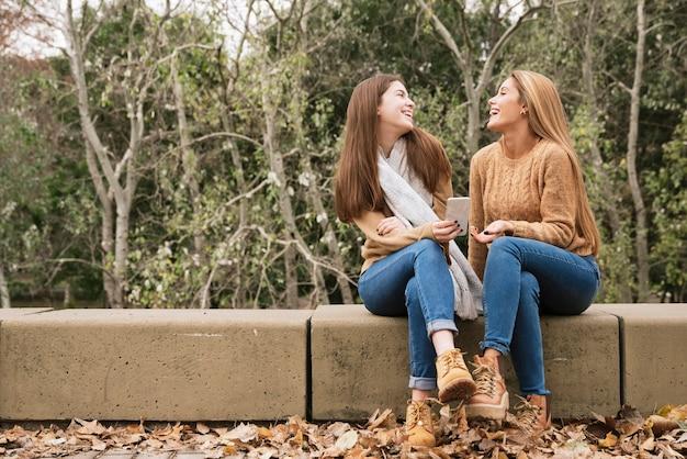 Dwie młode kobiety siedzą i rozmawiają w parku