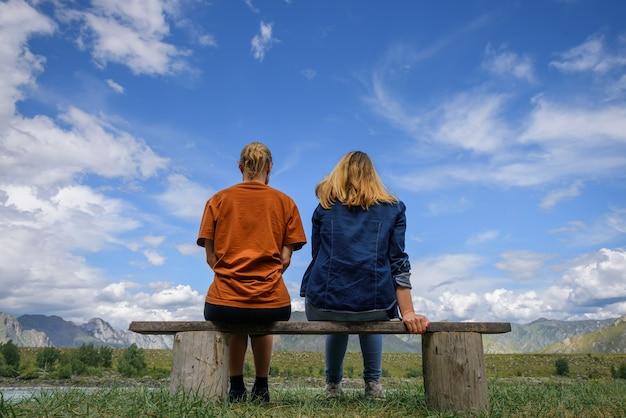 Dwie młode kobiety siedzą na drewnianej ławce, plecami do aparatu przed pięknym krajobrazem. przyjaciele podróżują, podziwiają wspaniały widok na pasmo górskie pod błękitnym niebem w słoneczny dzień.