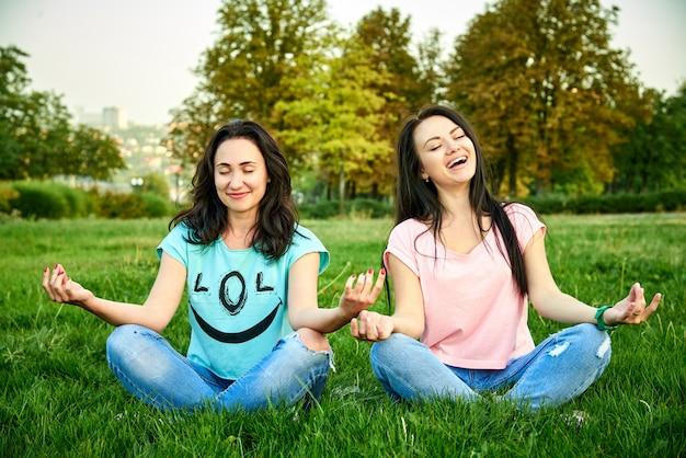 Dwie młode kobiety siedzą na zielonej trawie w pozycji lotosu z zamkniętymi oczami i uśmiechnięte.