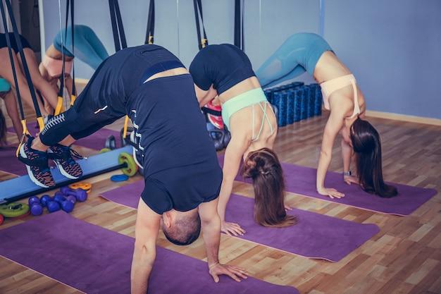 Dwie młode kobiety sprawny ćwiczeń na siłowni z trenerem fitness.