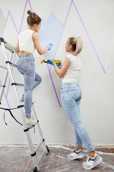 Dwie młode kobiety, stojąc na drabinie, malują ściany wałkiem do malowania i używają taśmy maskującej
