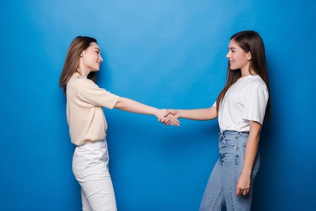 Dwie młode kobiety, stojące i niedbale ubrane, ściskające ręce i uśmiechające się na niebieskiej ścianie