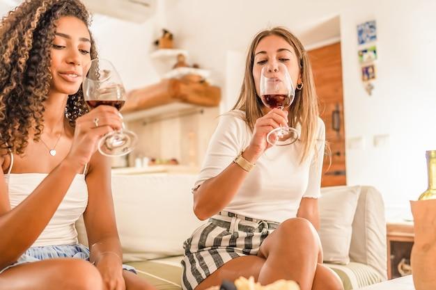 Dwie młode kobiety świętują w domu pijąc czerwone wino do szklanek, aby szczęśliwie wznieść toast. caucasion gay girl spajanie z jej afro-amerykanin kręcone dziewczyna picia na kanapie. pojęcie nadużywania alkoholu