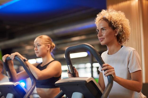 Dwie młode kobiety, trening na bieżniach w nowoczesnej siłowni