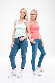 Dwie młode kobiety ubrane w t-shirty i dżinsy pozowanie. pojedynczo na białej ścianie
