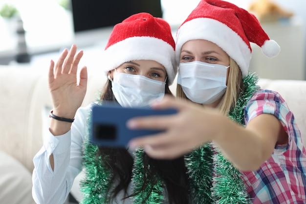 Dwie młode kobiety w czapkach mikołaja i maskach ochronnych na twarzach trzymają w domu portret telefonu
