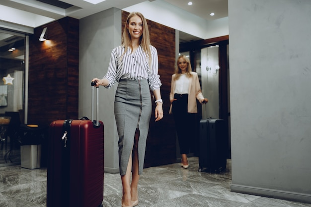 Dwie młode kobiety w formalnych ubraniach wchodzących do holu hotelu