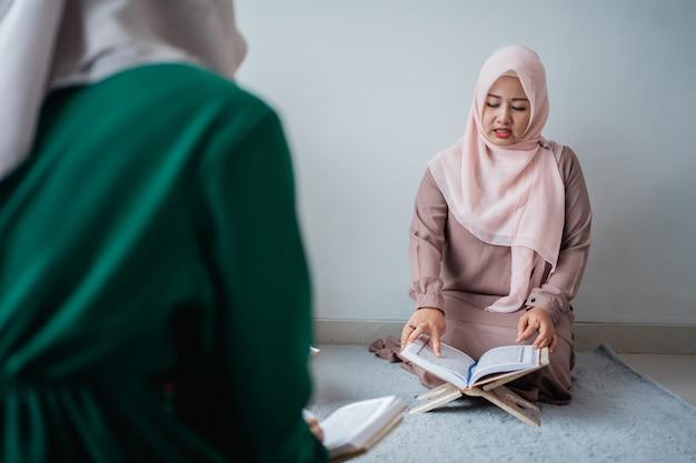 Dwie młode kobiety w hidżabach czytają razem świętą księgę al-koranu