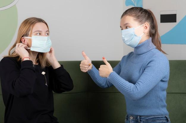 Dwie młode kobiety w maskach na twarz, mówiące sobie, że wszystko będzie dobrze.