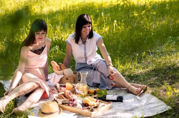 Dwie młode kobiety w parku na zewnątrz w słoneczny dzień. piknik na trawie z pizzą, chlebem, sokiem pomarańczowym, serem i owocami