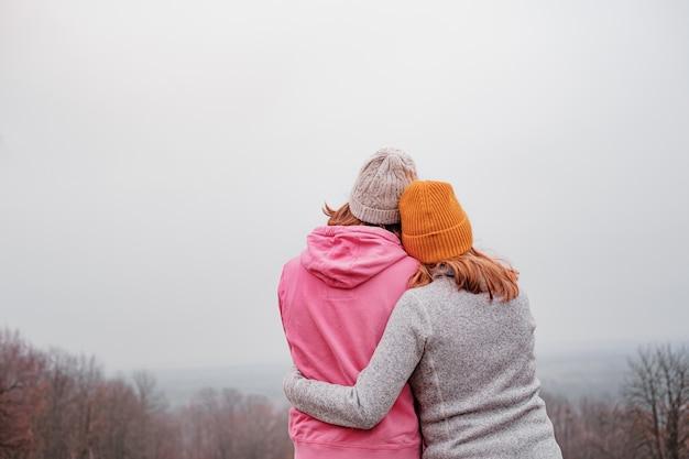 Dwie młode kobiety w przypadkowych ubraniach przytulają się na jesienne niebo. pojęcie wspólnoty i wsparcia, przyjaźni kobiety, związku homoseksualnego