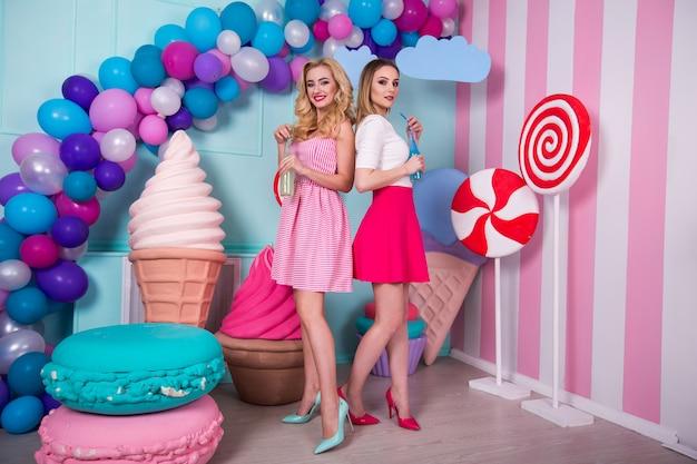 Dwie młode kobiety w różowych sukienkach piją sok w szklanej butelce.