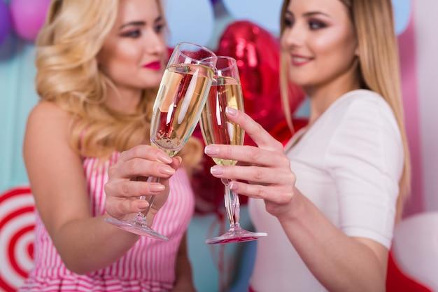 Dwie młode kobiety w różowych sukienkach trzymają kieliszki szampana.
