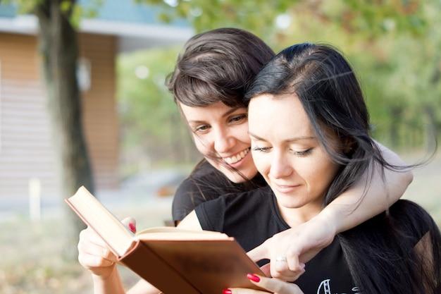 Dwie młode kobiety w ścisłym uścisku śmieją się razem z treści książki