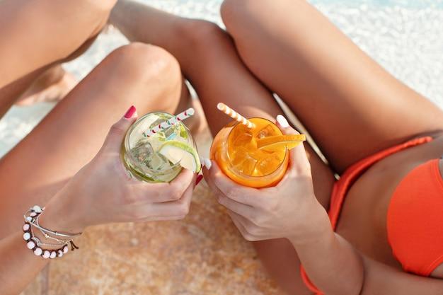 Dwie młode kobiety w strojach kąpielowych, relaks i picie tropikalnych koktajli w widoku z góry basen z bliska