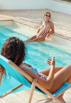 Dwie młode kobiety w strojach kąpielowych relaks w pobliżu basenu i rozmowa z bliska