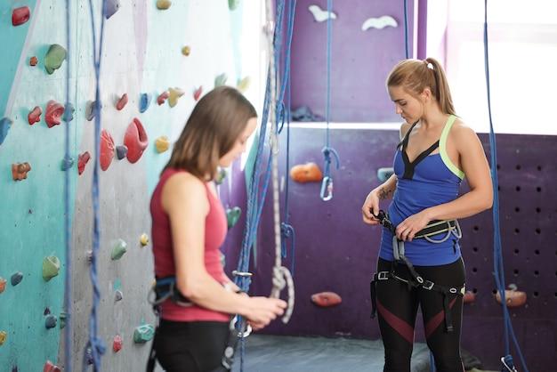 Dwie młode kobiety w strojach sportowych sprawdzają sprzęt wspinaczkowy podczas treningu na siłowni lub w centrum rekreacyjnym