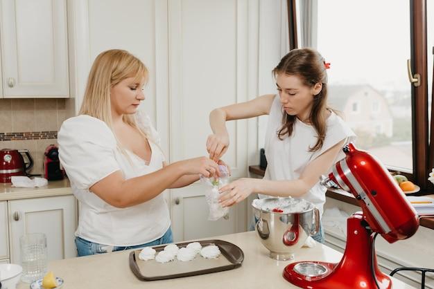 Dwie Młode Kobiety Wkładają Bezę Do Przezroczystej Plastikowej Torby W Kuchni Premium Zdjęcia