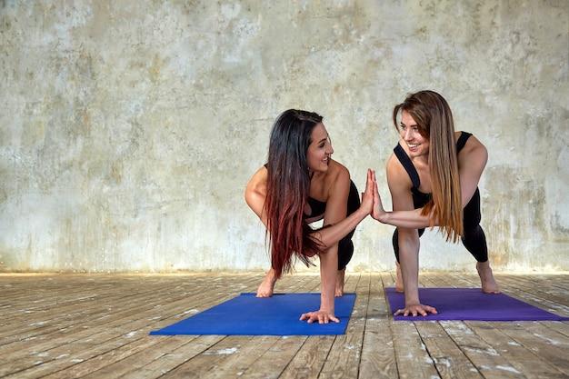 Dwie młode kobiety wykonują sparowane ćwiczenia w sali fitness. pozując i uśmiechając się do kamery, baw się dobrze, świetna atmosfera.