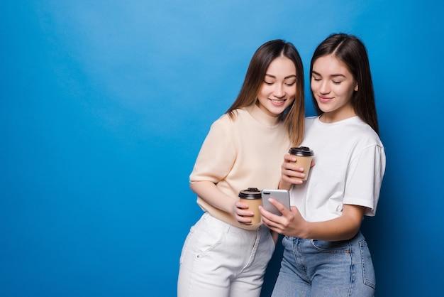 Dwie młode kobiety z filiżanką kawy, aby przejść na białym tle na niebieskiej ścianie