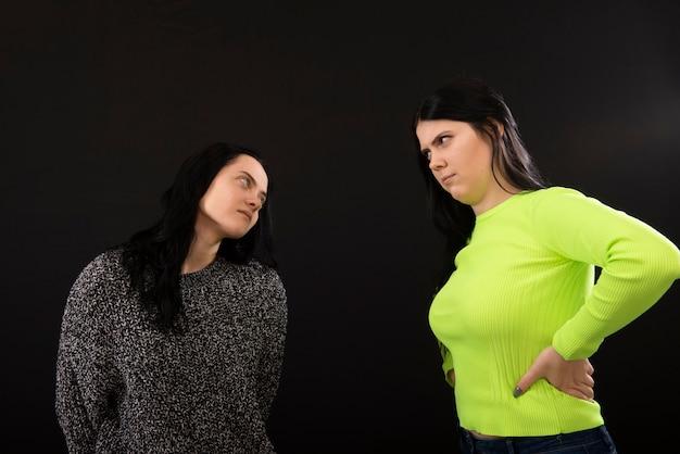 Dwie młode kobiety z gniewnymi twarzami patrząc na siebie na białym tle