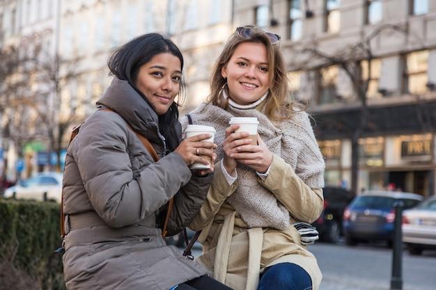 Dwie młode kobiety z gorącym napojem