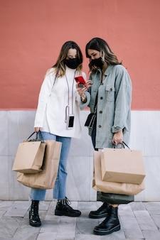 Dwie młode kobiety z maskami patrząc na telefon komórkowy.