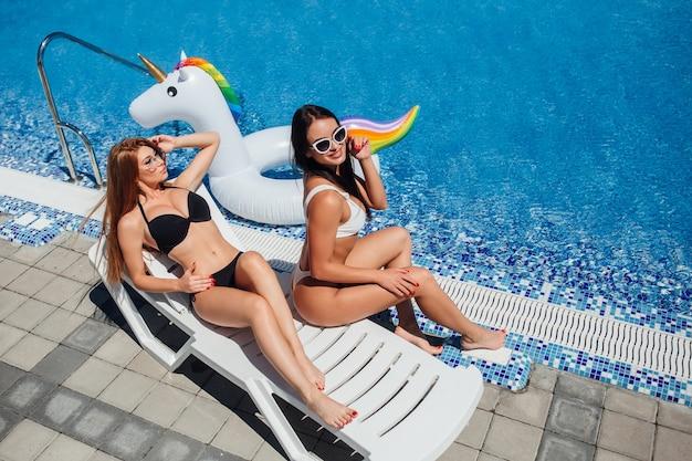 Dwie młode kobiety z postaciami opalają się przy basenie na leżakach jednorożca.