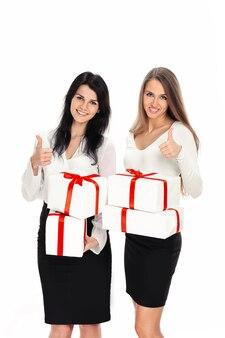 Dwie młode kobiety z pudełkami prezentów pokazujące aprobaty. na białym tle