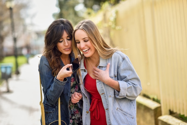 Dwie młode kobiety za pomocą rozpoznawania głosu na zewnątrz telefonu