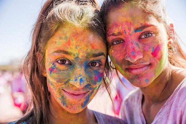 Dwie młode kobiety zakryły twarz kolorowym proszkiem holi